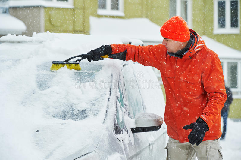 Man cleaning car from snow. Young man cleaning and removing show from car windscreen of automobile during winter royalty free stock photo