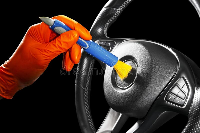 A man cleaning car steering wheel with brush. Car detailing or valeting concept. Selective focus. Car detailing. Cleaning with spo. Nge. Worker cleaning. Car stock photos