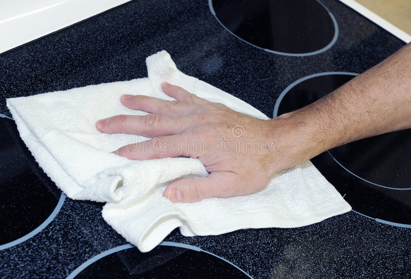 Man cleaning cooktop. Man's hand with cotton terry towel cleaning ceramic cooktop stock photo