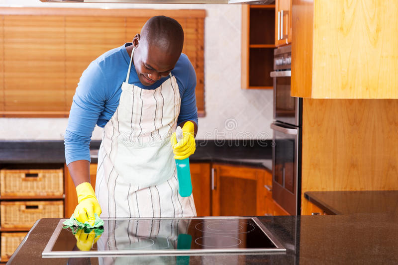 Man cleaning cooktop. Busy young african man cleaning cooktop at home stock photography