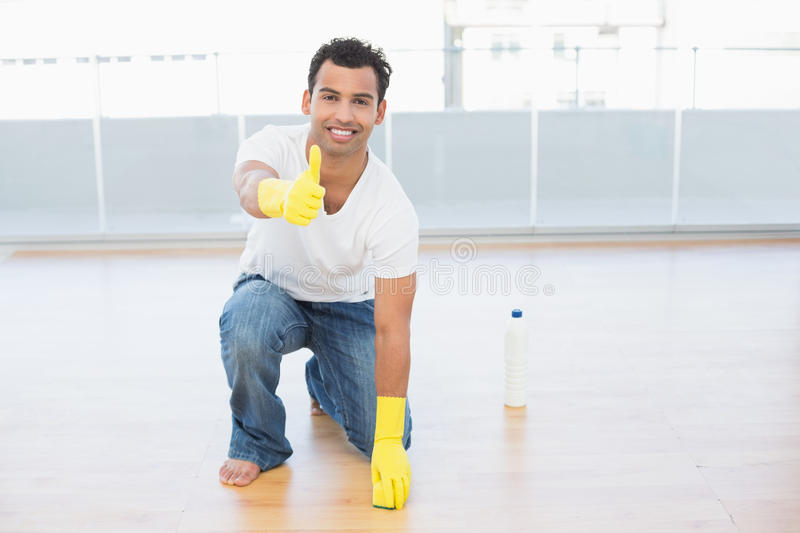 Man cleaning the floor while gesturing thumbs up at house stock photo