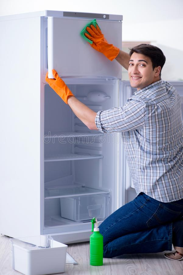 The man cleaning fridge in hygiene concept. Man cleaning fridge in hygiene concept stock photos
