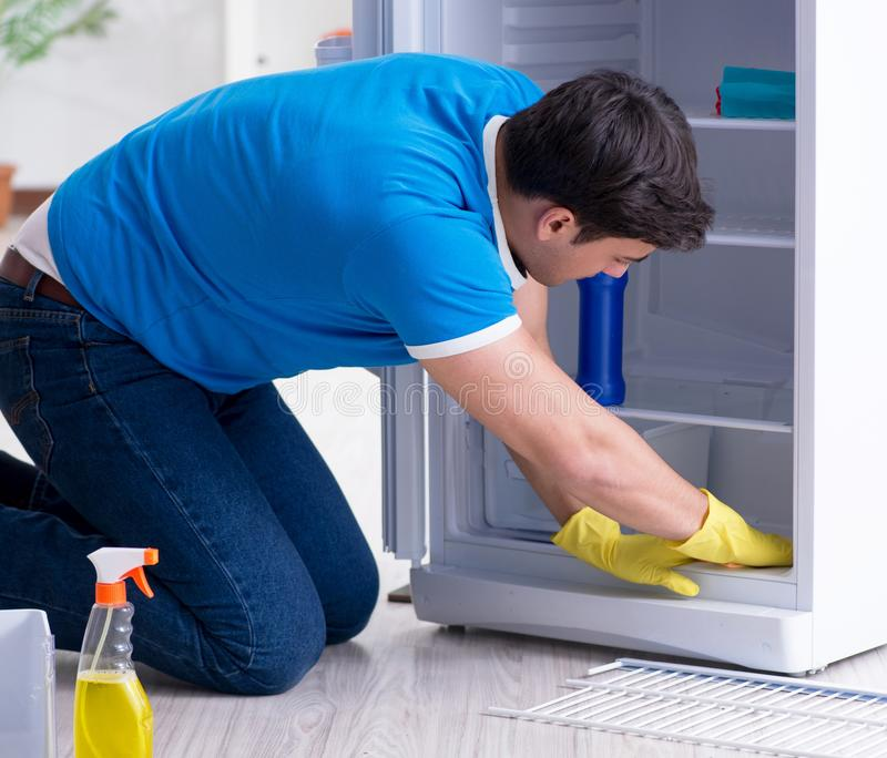 Man cleaning fridge in hygiene concept royalty free stock photography