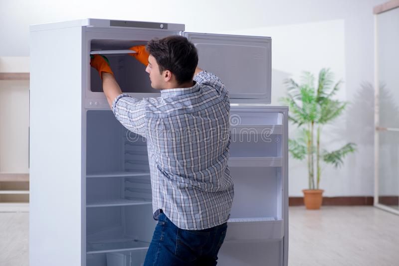 The man cleaning fridge in hygiene concept. Man cleaning fridge in hygiene concept royalty free stock photos