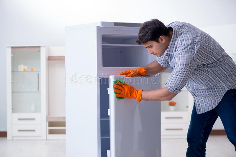 The man cleaning fridge in hygiene concept. Man cleaning fridge in hygiene concept royalty free stock image