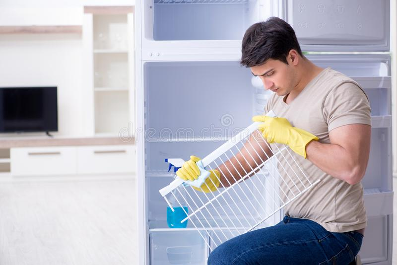 The man cleaning fridge in hygiene concept. Man cleaning fridge in hygiene concept stock photography