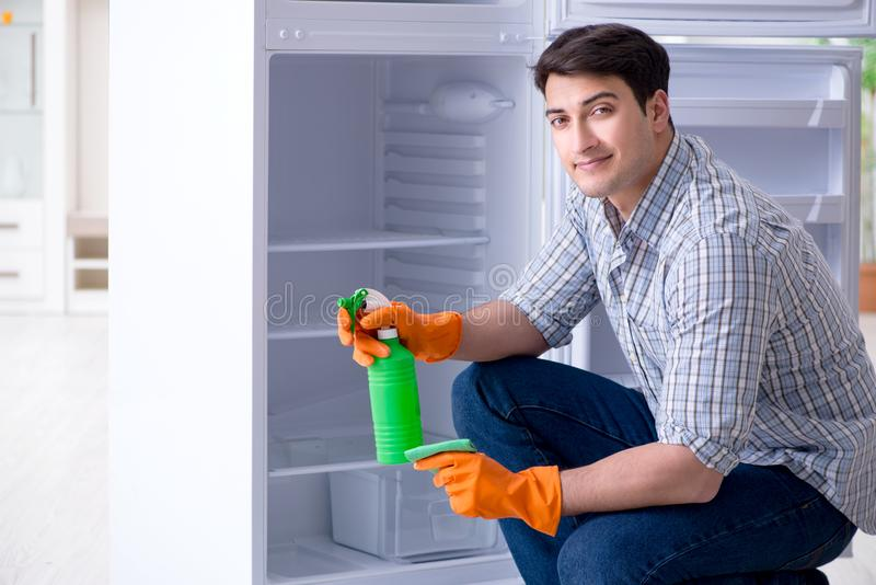The man cleaning fridge in hygiene concept. Man cleaning fridge in hygiene concept stock images