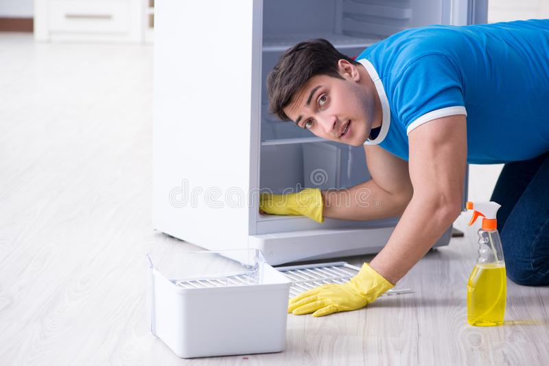 The man cleaning fridge in hygiene concept. Man cleaning fridge in hygiene concept stock image