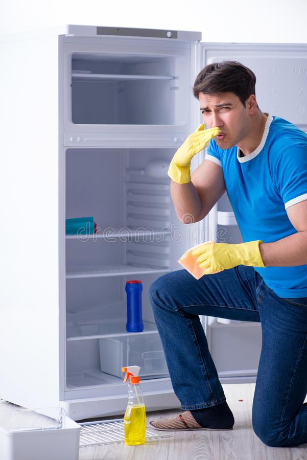 The man cleaning fridge in hygiene concept. Man cleaning fridge in hygiene concept royalty free stock photography