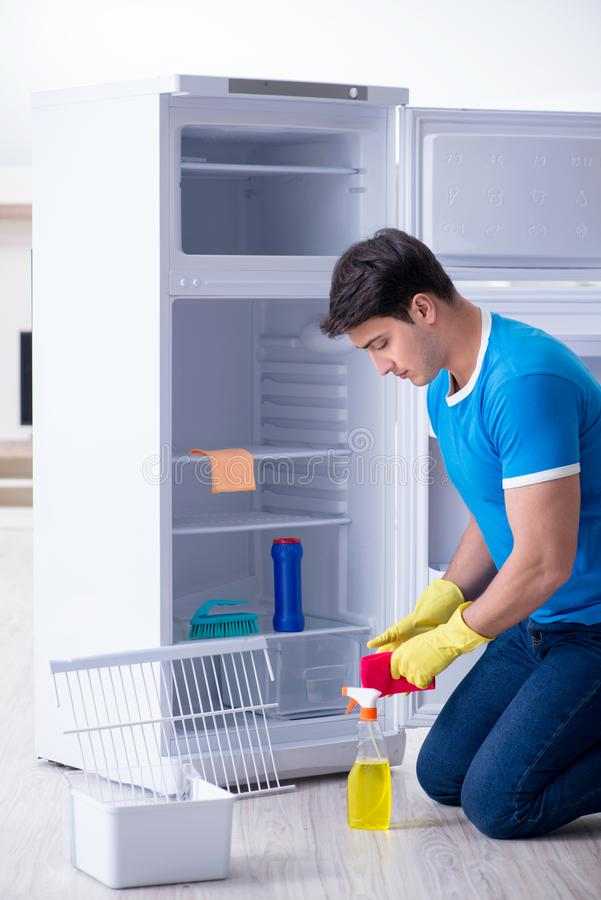The man cleaning fridge in hygiene concept. Man cleaning fridge in hygiene concept royalty free stock photo