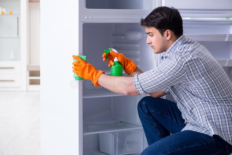 The man cleaning fridge in hygiene concept. Man cleaning fridge in hygiene concept royalty free stock images