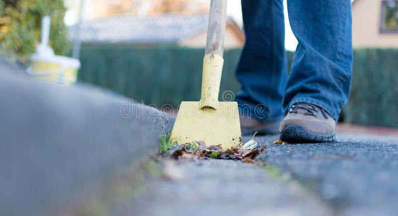Man is cleaning the gutter. Man is cleaning the street gutter stock photos