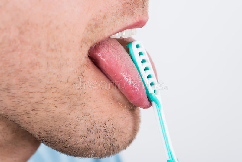 Man Cleaning Her Tongue. Close-up Of Young Man Cleaning His Tongue With Scraper royalty free stock photos