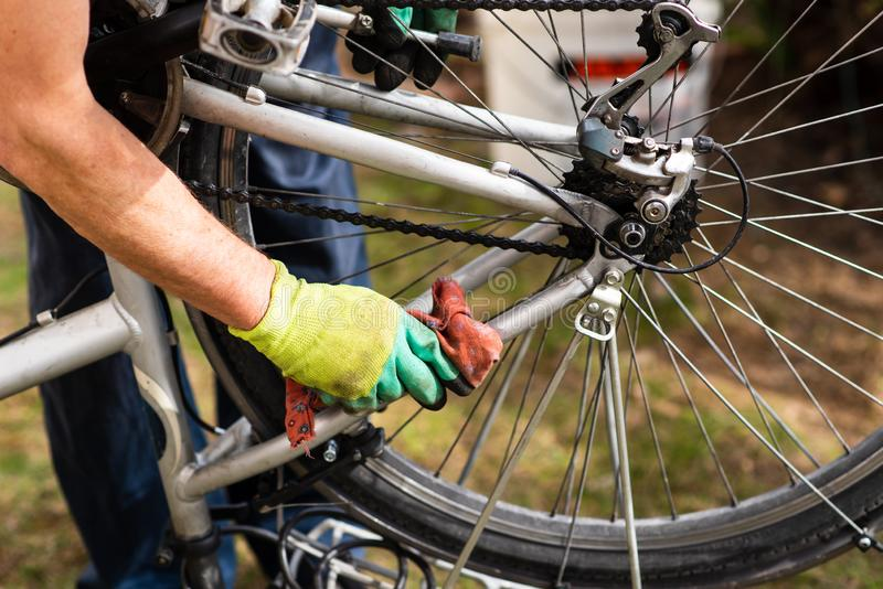 Man cleaning his bicycle for the new season. Man cleaning his bicycle for the new driving season, maintaining, male, drive, fix, fixing, mechanic, maintenance royalty free stock photos