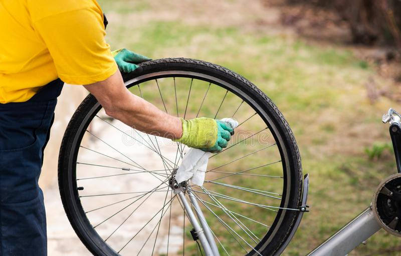 Man cleaning his bicycle for the new season. Man cleaning his bicycle for the new driving season, maintaining, male, drive, fix, fixing, mechanic, maintenance stock photography