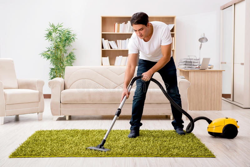 The man cleaning home with vacuum cleaner stock photography