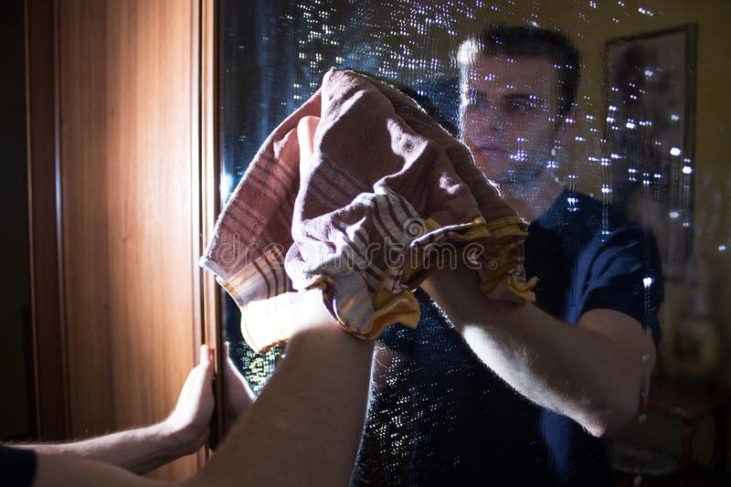 Man is cleaning the house, washes glass, mirror, cleaning agent, dirty glass stock images