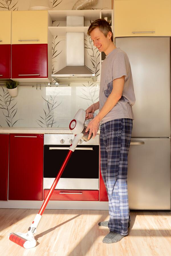 Man cleaning house with wireless vacuum cleaner foto de archivo