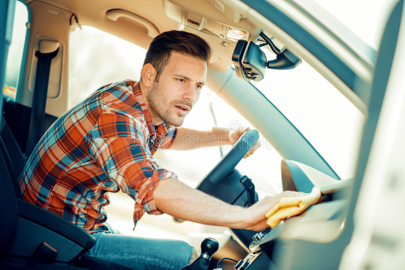 Man cleaning the interior of his car. Outdoors stock photos