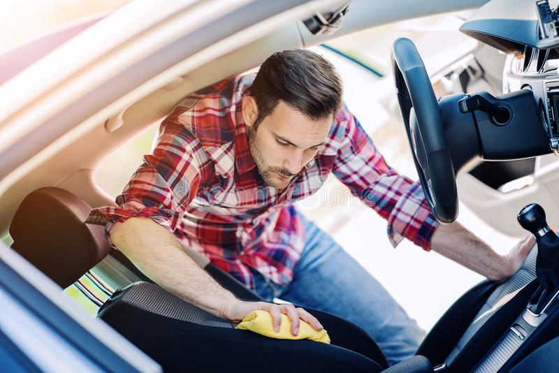Man cleaning the interior of his car. Young man cleaning his car outdoors.Man cleaning the interior of his car stock photography
