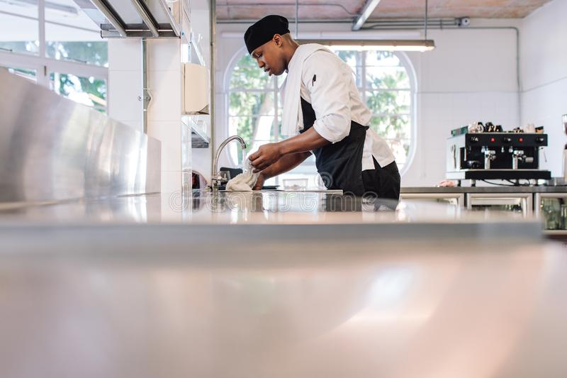 Man cleaning the kitchen counter. Restaurant employee soaking a cloth in water for cleaning counter. Man working at commercial kitchen royalty free stock photos