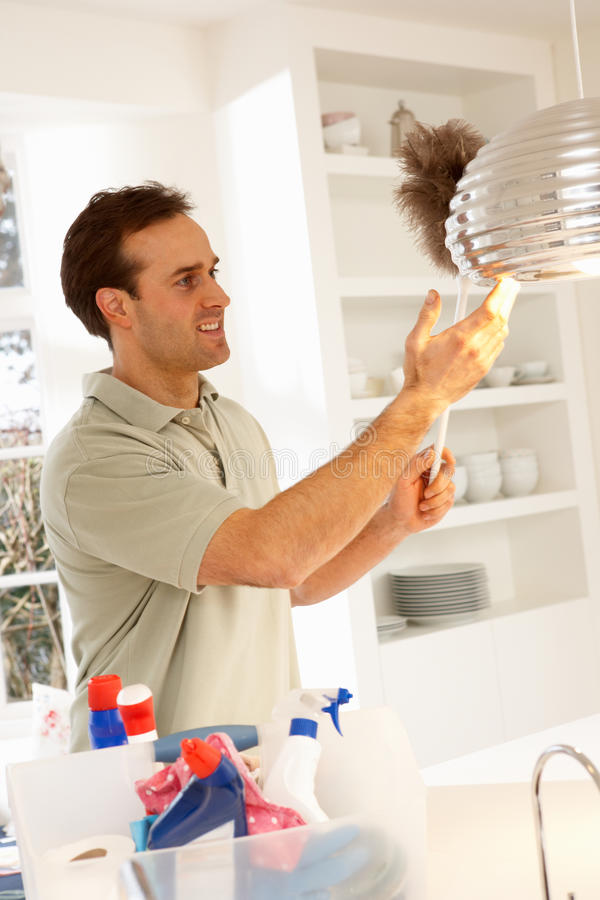 Man Cleaning Light Fitting With Feather Duster. Smiling stock images