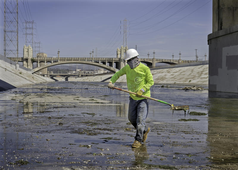 Man Cleaning Los Angeles River, California. A man holds a shovel full of debris as he works at his job cleaning the Los Angeles River, in downtown L.A royalty free stock images