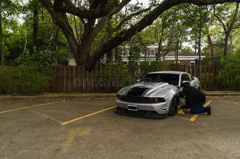 Man Cleaning a Silver Ford Mustang royalty free stock photo