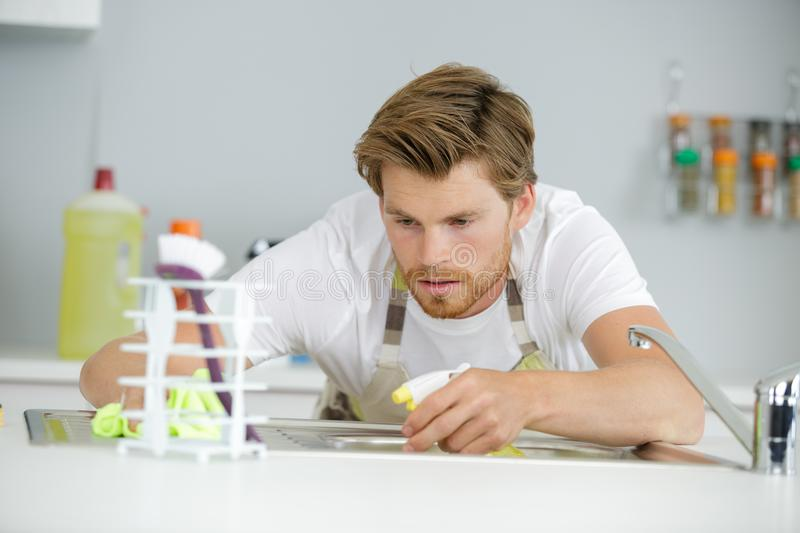 Man cleaning the sink. Cleaning royalty free stock photography