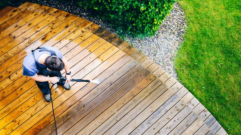 man cleaning terrace with a power washer - high water pressure c royalty free stock images
