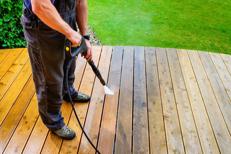 Man cleaning terrace with a power washer - high water pressure c royalty free stock photography