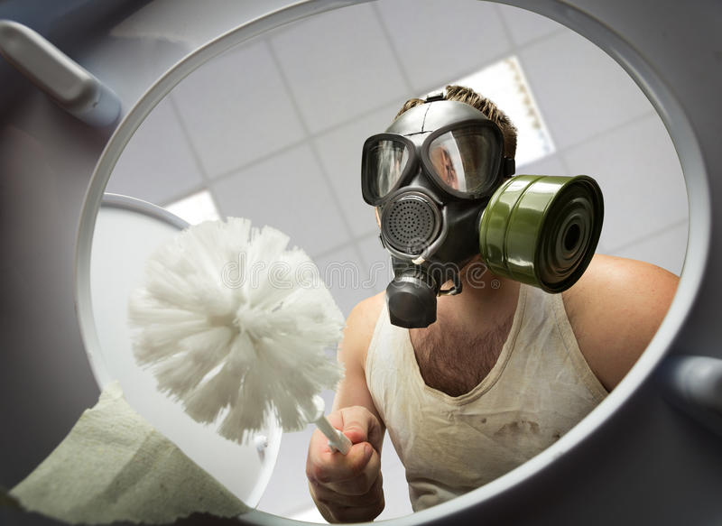 Man cleaning the toilet bowl. Man in gas mask with brush cleaning the toilet bowl royalty free stock photography