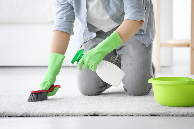 Man cleaning white carpet with brush. In living room stock image