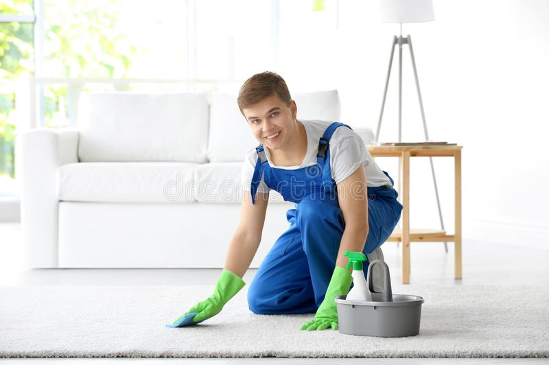 Man cleaning white carpet in living room stock photography