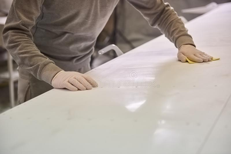 Man is cleaning white plate. Plane cleaning royalty free stock photo