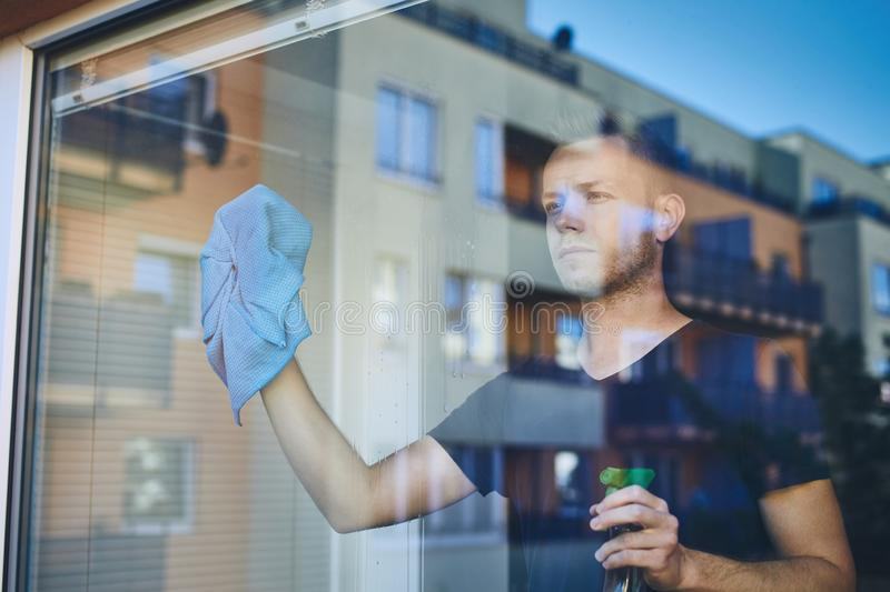 Man cleaning window at home stock photography