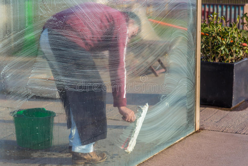 Man cleaning windows glass pane with foam. Restaurant staff takeing care of front glass pane Man cleaning windows glass pane with foam royalty free stock images