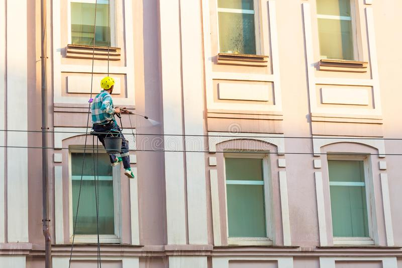 Man cleaning windows and wall on old city bulding stock photography