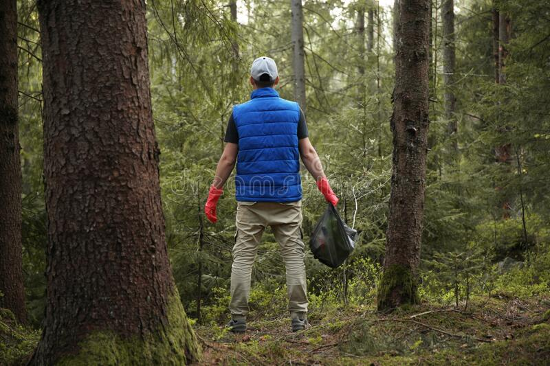 Man cleans garbage and plastic bottle in forest. Green volunteering. Caring for environment royalty free stock photography