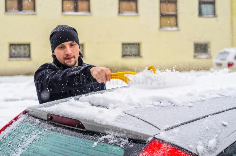 Man cleans his car from the snow. Young man in black coat cleans his car with yellow brush during snowfall. Winter inclement weather royalty free stock photography