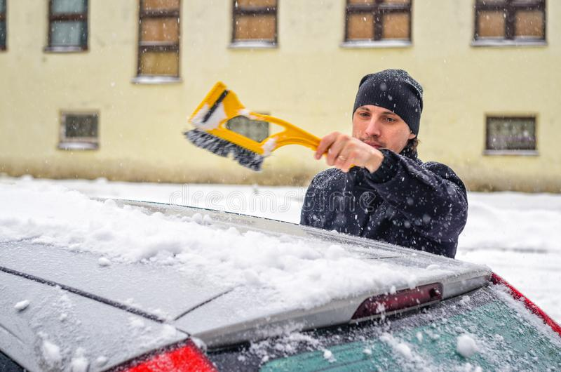 Man cleans his car from the snow. Young man in black coat cleans his car with yellow brush during snowfall. Winter inclement weather royalty free stock photo
