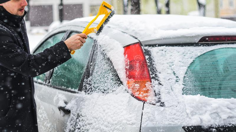 Man cleans his car from the snow. Young man in black coat cleans his car with yellow brush during snowfall. Winter inclement weather stock photography