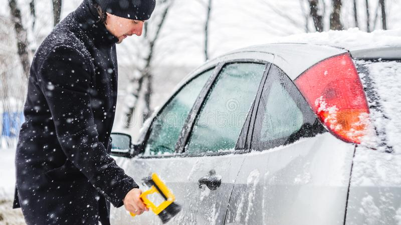 Man cleans his car from the snow. Young man in black coat cleans his car with yellow brush during snowfall. Winter inclement weather stock image