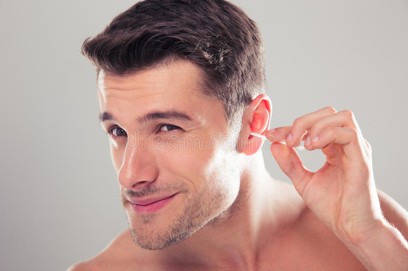 Man cleans his ear with a cotton swab stock photo