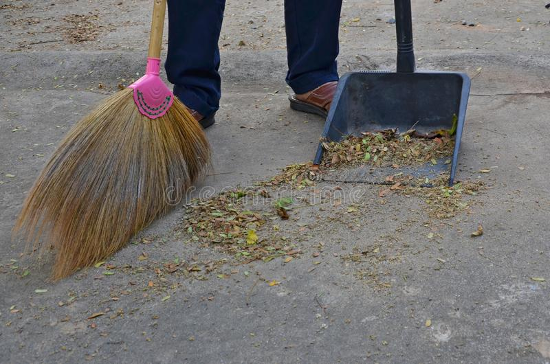 Cleaning concrete floor with grass broom and black plastic dustpan royalty free stock images