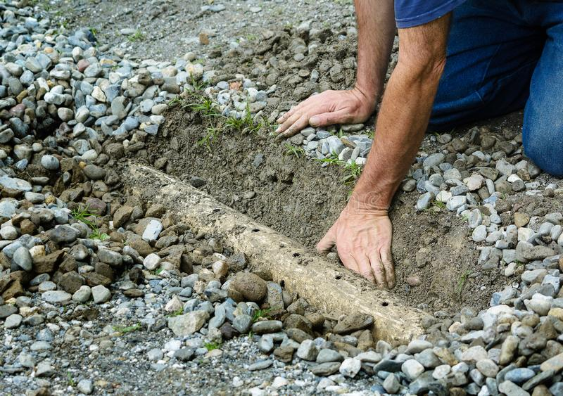 Man clears drainage ditch in driveway. Homeowner clears around a french drain pipe after it clogged with mud after heavy rainfall royalty free stock photography