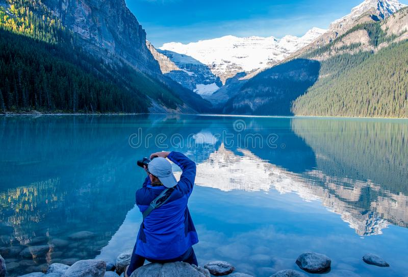Photography in lake Louise Alberta. A man clicking photograph beside lake Louise in Banff national park royalty free stock photos