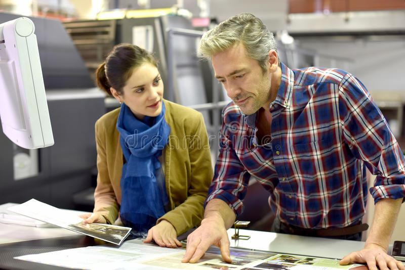 Man and client in printing industry checking on prints. Man in printing house showing client printed documents royalty free stock photography