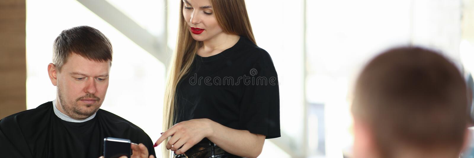 Man Client Showing on Phone to Woman Hairdresser stock photos