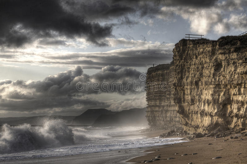 Man on Cliff. Man standing at edge of cliff looking out to stormy ocean and sky stock photography